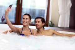 Couples heureux appréciant le jacuzzi dans la station thermale d'hôtel Photo libre de droits