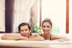 Couples heureux appréciant le jacuzzi dans la station thermale d'hôtel Image stock