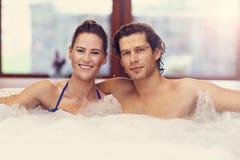 Couples heureux appréciant le jacuzzi dans la station thermale d'hôtel Images libres de droits