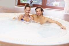 Couples heureux appréciant le jacuzzi dans la station thermale d'hôtel Image libre de droits