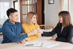 Couples heureux asiatiques obtenant la clé avec l'agent d'agent immobilier avec f de sourire images libres de droits