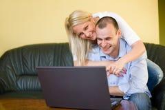 Couples heureux attrayants utilisant l'ordinateur portatif à la maison. Image libre de droits
