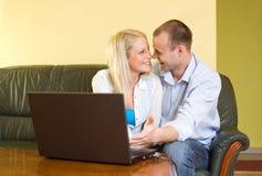 Couples heureux attrayants utilisant l'ordinateur portatif à la maison. Photographie stock libre de droits