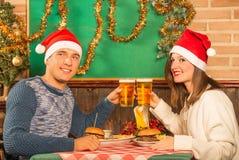 Couples heureux au restaurant avec des chapeaux de Santa photographie stock libre de droits