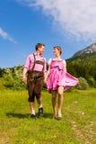 Couples heureux augmentant dans le pré alpestre Images libres de droits