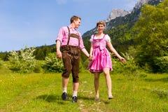 Couples heureux augmentant dans le pré alpestre Images stock