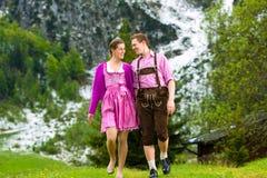 Couples heureux augmentant dans le pré alpin Image libre de droits