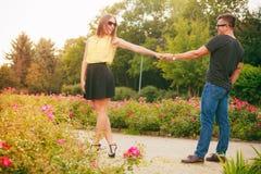 Couples heureux autour des fleurs Image stock