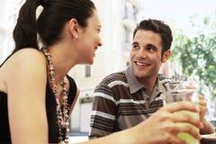 Couples heureux ayant des boissons au café de trottoir Image stock
