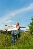 Couples heureux ayant l'amusement à l'extérieur en été Images libres de droits