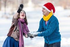 Couples heureux ayant l'amusement à l'horaire d'hiver extérieur Photographie stock libre de droits