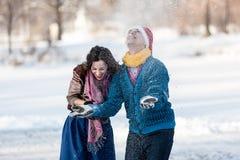 Couples heureux ayant l'amusement à l'horaire d'hiver extérieur Photographie stock