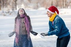 Couples heureux ayant l'amusement à l'horaire d'hiver extérieur Photo libre de droits