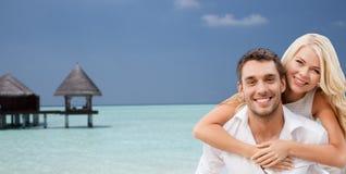 Couples heureux ayant l'amusement au-dessus de la plage avec le pavillon Images stock