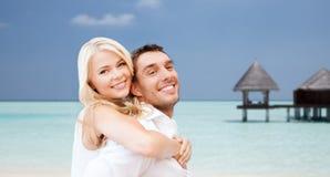 Couples heureux ayant l'amusement au-dessus de la plage avec le pavillon Image libre de droits