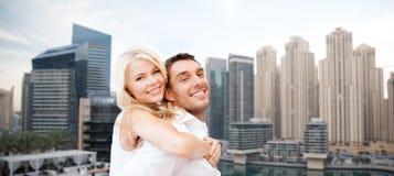 Couples heureux ayant l'amusement au-dessus du fond de ville du Dubaï Images libres de droits