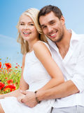 Couples heureux ayant l'amusement au-dessus du gisement de fleurs de pavot Images stock