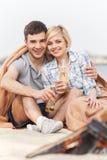Couples heureux ayant l'amusement autour du feu Photos stock
