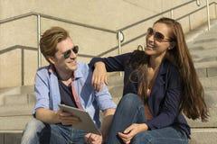 Couples heureux ayant l'amusement avec la tablette Photos stock