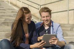 Couples heureux ayant l'amusement avec la tablette Photo stock