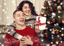 Couples heureux ayant l'amusement dans la décoration de Noël à la maison Soirée du Nouveau an, arbre de sapin ornated Vacances d' Photo libre de droits