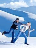 Couples heureux ayant l'amusement dans la neige Photo libre de droits