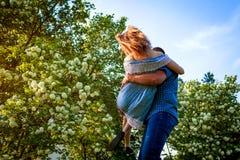 Couples heureux ayant l'amusement dans le jardin de floraison L'homme tient son amie dans des mains et tourne au coucher du solei Photo stock
