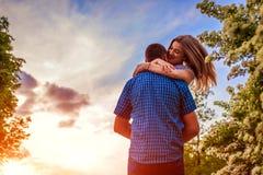 Couples heureux ayant l'amusement dans le jardin de floraison L'homme tient son amie dans des mains et tourne au coucher du solei Photo libre de droits