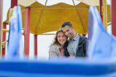 Couples heureux ayant l'amusement dans le terrain de jeu regardant l'appareil-photo Image libre de droits