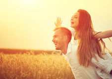 Couples heureux ayant l'amusement dehors sur le champ de blé Image libre de droits