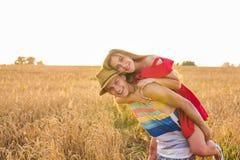 Couples heureux ayant l'amusement dehors sur le champ de blé au-dessus du coucher du soleil Famille joyeuse riante ensemble Conce Images libres de droits