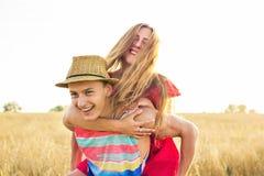 Couples heureux ayant l'amusement dehors sur le champ de blé au-dessus du coucher du soleil Famille joyeuse riante ensemble Conce Image stock
