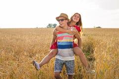 Couples heureux ayant l'amusement dehors sur le champ de blé au-dessus du coucher du soleil Famille joyeuse riante ensemble Conce Photographie stock