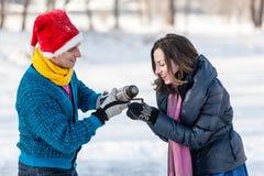 Couples heureux ayant l'amusement et buvant du thé chaud sur la piste dehors Image stock