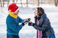 Couples heureux ayant l'amusement et buvant du thé chaud sur la piste dehors Image libre de droits