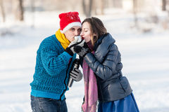 Couples heureux ayant l'amusement et buvant du thé chaud sur la piste dehors Photos stock
