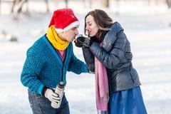 Couples heureux ayant l'amusement et buvant du thé chaud sur la piste dehors Photographie stock libre de droits