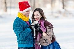 Couples heureux ayant l'amusement et buvant du thé chaud sur la piste dehors Photographie stock