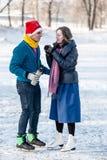 Couples heureux ayant l'amusement et buvant du thé chaud sur la piste dehors Images stock