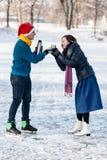Couples heureux ayant l'amusement et buvant du thé chaud sur la piste dehors Photos libres de droits