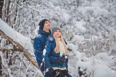 Couples heureux ayant l'amusement et l'embrassant dehors dans le parc de neige Vacances de l'hiver photos stock