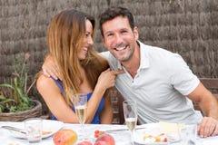 Couples heureux ayant l'amusement et la nourriture dans le jardin Photos libres de droits