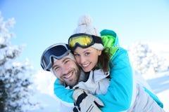 Couples heureux ayant l'amusement sur des pentes de ski Image stock