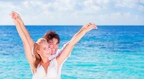 Couples heureux ayant l'amusement sur la plage Photographie stock libre de droits