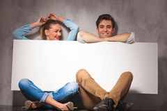 Couples heureux ayant l'amusement tout en présentant un grand conseil vide Images libres de droits