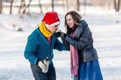 Couples heureux ayant le patinage de glace d'amusement et buvant du thé chaud du Th Images stock