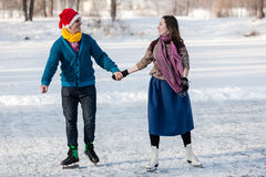 Couples heureux ayant le patinage de glace d'amusement sur la piste dehors Photos libres de droits