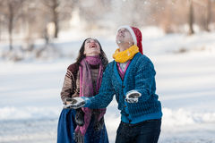Couples heureux ayant le patinage de glace d'amusement sur la piste dehors Photo stock