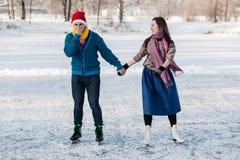 Couples heureux ayant le patinage de glace d'amusement sur la piste dehors Images libres de droits