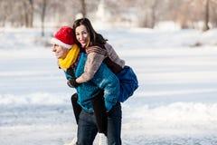 Couples heureux ayant le patinage de glace d'amusement sur la piste dehors Images stock